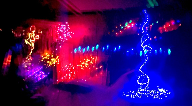 Some of the brilliant effects of holiday lights come from the reflections, on water and window glass, compounding the joy.